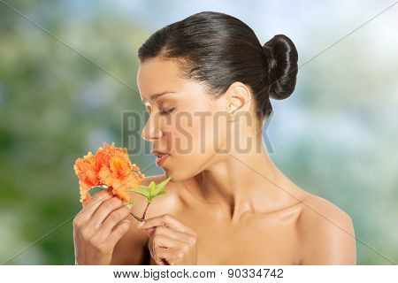 Beautiful exotic spa woman smelling orange flower.