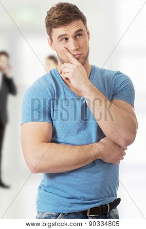 Young handsome pensive man with finger under chin.