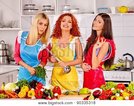 Happy three women preparing food at kitchen. Many vegetable on table.