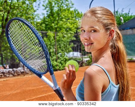 Girl sportsman with racket and ball on  tennis court. Green tree ang blue sky on background. Looks over her shoulder