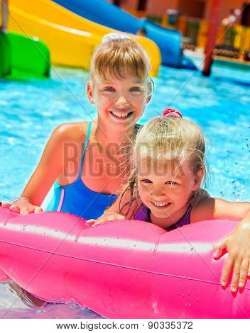 Female children sitting on pink inflatable ring in swimming pool.