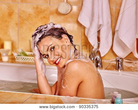 Happy woman washing hair in bubble bath. A  lot of water.