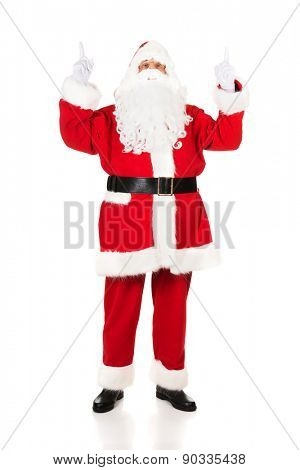 Full length Santa Claus pointing his hands up.