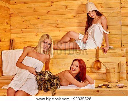 Group women sitting on bench in sauna.