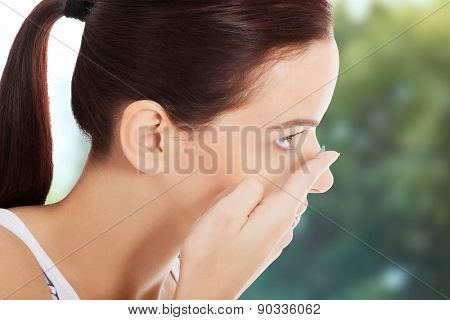 Woman applying contact lens in her eye.