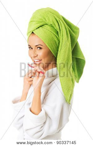 Spa woman in bathrobe brushing teeth.