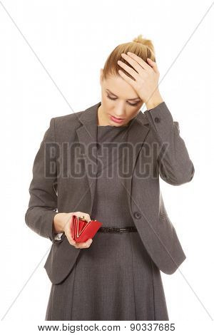 Shocked woman looking into her empty wallet.