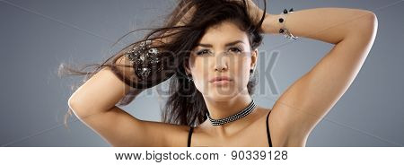 Closeup portrait of attractive sexy woman with hand in hair, looking at camera.