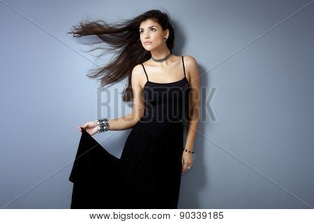 Attractive young woman posing by grey wall in black dress, windtorn long hair, looking away.