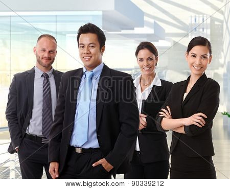 Portrait of happy interracial business team standing in office lobby, smiling.