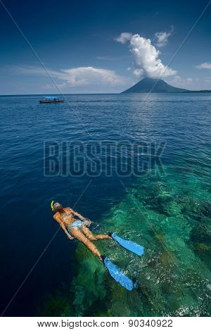 Lady snorkeling over reef wall in the area of the island of Bunaken, Sulawesi, Indonesia