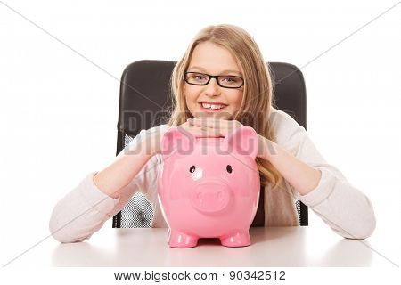 Happy teenage woman with piggybank on the table
