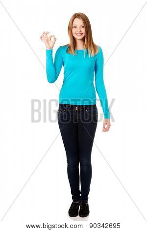 Happy teenage woman showing perfect sign