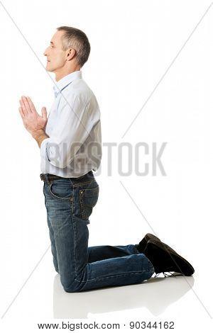 Handsome mature man praying to God on knees.