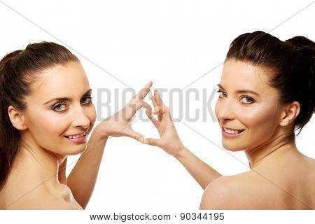 Two beautiful women making heart with fingers.