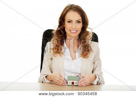 Businesswoman with small house by a desk.