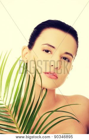 Portrait of nude woman with palm leaf.