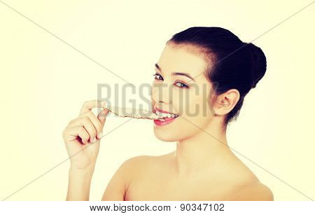 Happy young woman eating crisp bread