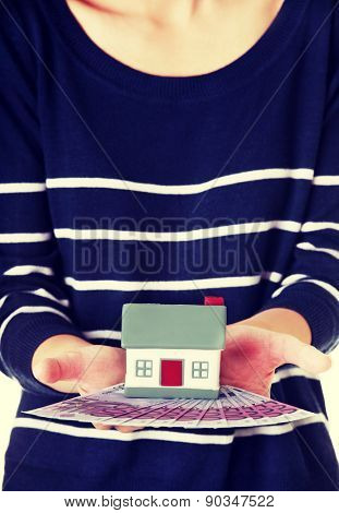 Woman holding a house model and euro bills.