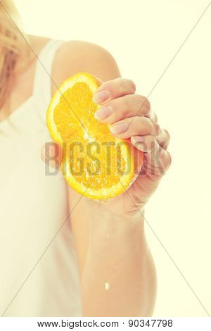 Woman squeezing juice from an orange.