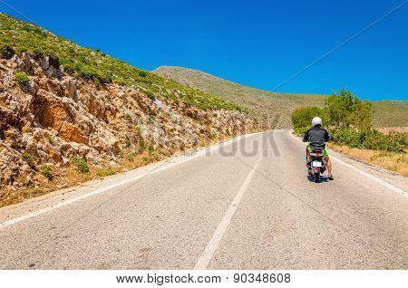 Young man driving scooter on empty asphalt road
