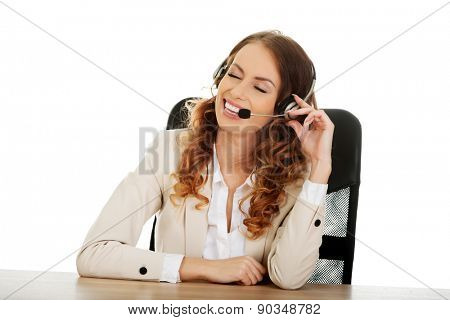 Smiling call center woman by a desk.