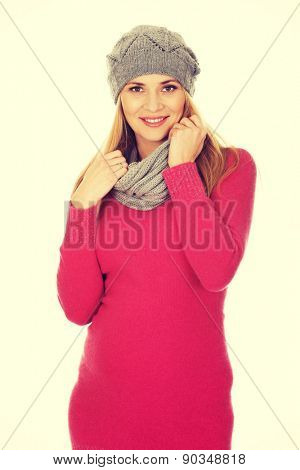 Pregnant woman in outerwear touching her belly