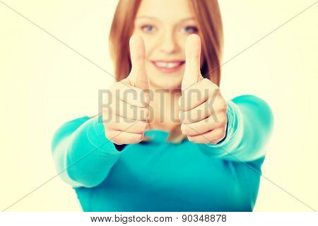 Happy teenager showing thumbs up with both hands