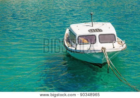 Small empty white motorboat on anchor