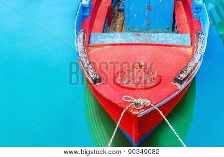 Empty red wooden boat with blue broadside