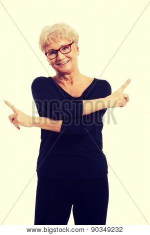 Happy senior woman pointing on both sides