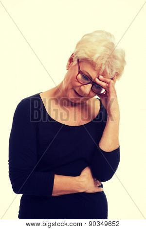 Senior worried woman touching her head