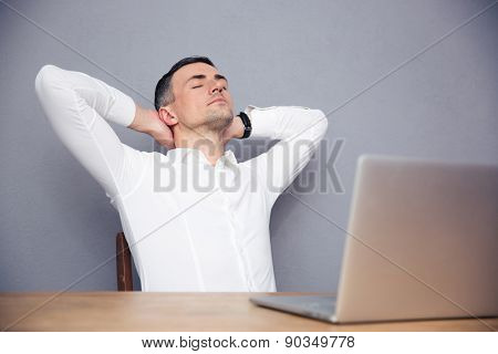 Handsome businessman sleeping at the table with laptop over gray background