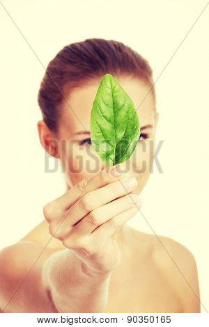 Nude woman holding a green leaf.