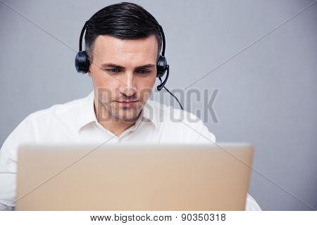 Businessman using laptop in headphones over gray background