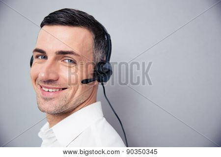 Cheerful businessman in headphones standing over gray background and looking at camera