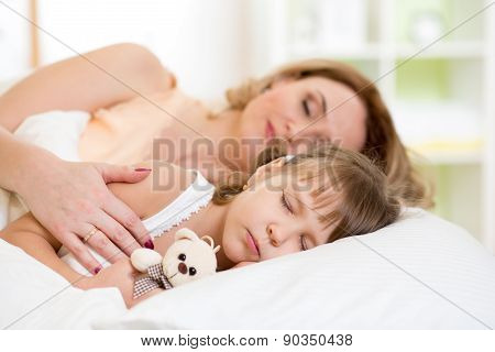 Child with mother preparing for napping on bed