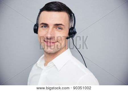 Happy young businessman in headphones over gray background. Looking at camera