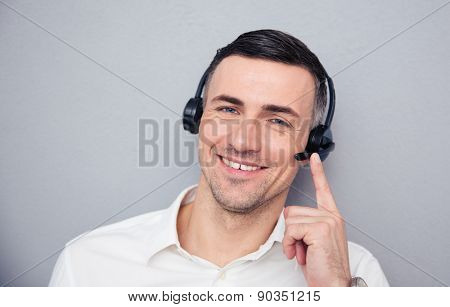 Happy young male operator in headphones looking at camera. Standing over gray background