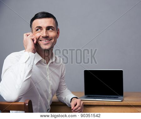Happy businessman talking on the phone and looking away