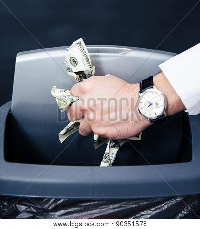 Concept image of a businessman hands throwing US dollar bills in trash bin