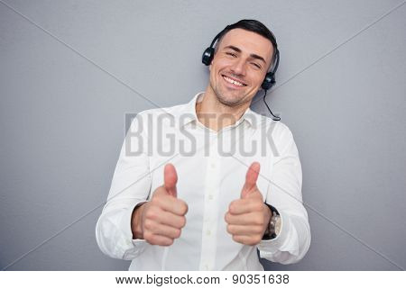 Happy male operator in headphones showing thumbs up over gray background. Looking at camera
