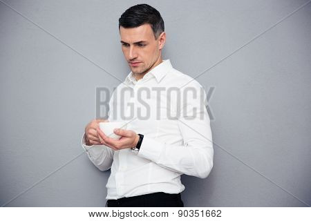 Pensive businessman holding cup of coffee over gray background and looking away