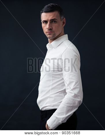 Portrait of a pensive businessman wearing in shirt standing over black background. Looking at camera