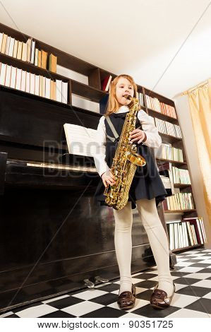 Girl in school uniform plays on alto saxophone