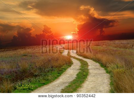 road in steppe against sunset in sky