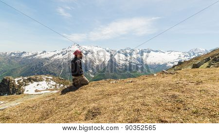 Hiker Kneeling On The Mountain Top