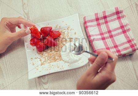 Fresh strawberries, chocolate and whipped cream on a plate. Female hand taking strawberryFresh straw