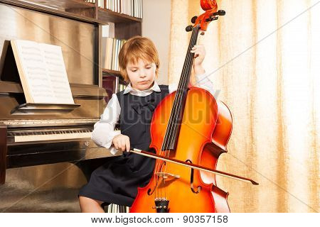 Beautiful girl in school uniform plays on cello