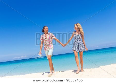 Beach couple walking on romantic travel honeymoon vacation summer holidays romance. Young happy lovers, holding hands embracing outdoors.